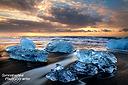 Die bläulich schillernden Eisberge am Strand von Jökulsarlon - die Sonne zeigte sich bei unseren zwei Sonnenaufgängen immer nur hinter Wolken, aber dort dafür umso surrealer und dramatischer.