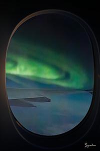 Polarlichter durch das Fenster im Flugzeug können unglaublich grün erscheinen